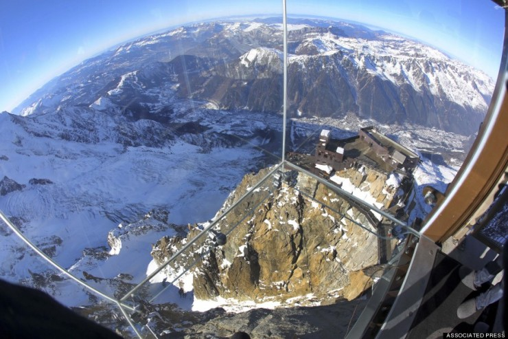 In this photo taken on Tuesday, Dec. 17, 2013, mountains are seen through a glass cage named 'Pas dans le Vide' (Step into the Void) at the top of the Aiguille du Midi peak (3842-meters high or 12,604 feet), in the French Alps, during a press visit. Visitors can enjoy the view of Mont Blanc, Europe's highest mountain, from the platform. The attraction opens Saturday. (AP Photo/Alexis Moro)