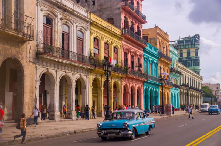 A blue oldtimer taxi is driving through Habana Vieja.