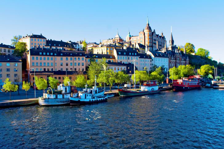 Sweden Old city buildings and old boats on water under blue sky