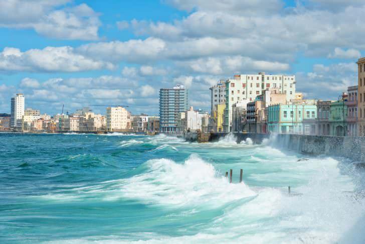 The Havana skyline with big sea waves crashing on the Malecon seawall.