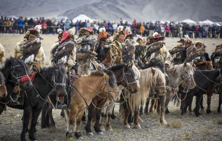 Eagle hunter riding a horse with his Altai Golden Eagle