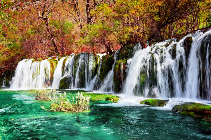 Beautiful waterfall and azure lake with crystal clear water among fall woods in Jiuzhaigou nature reserve