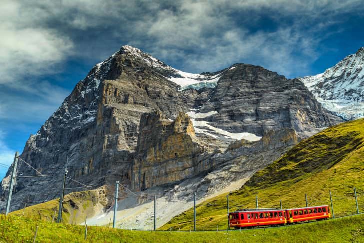 Spectacular famous electric red tourist train coming down from the Jungfraujoch station