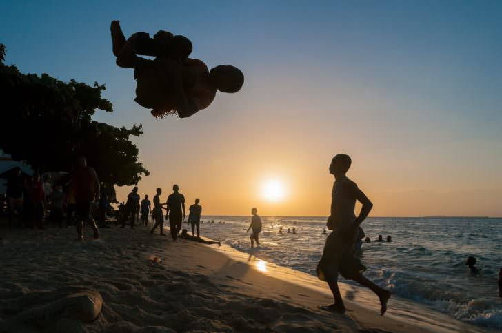 Young african man doing somersaults on the beach in Stone town, Zanzibar