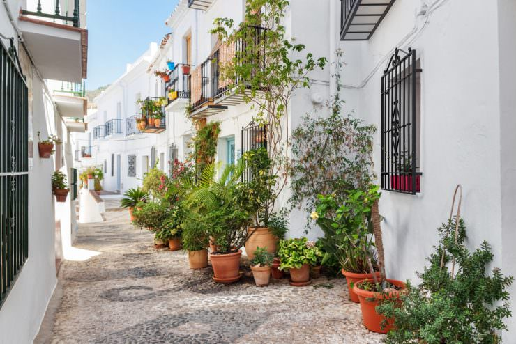 Picturesque narrow street decorated with plants. Frigiliana, Andalusia, Spain