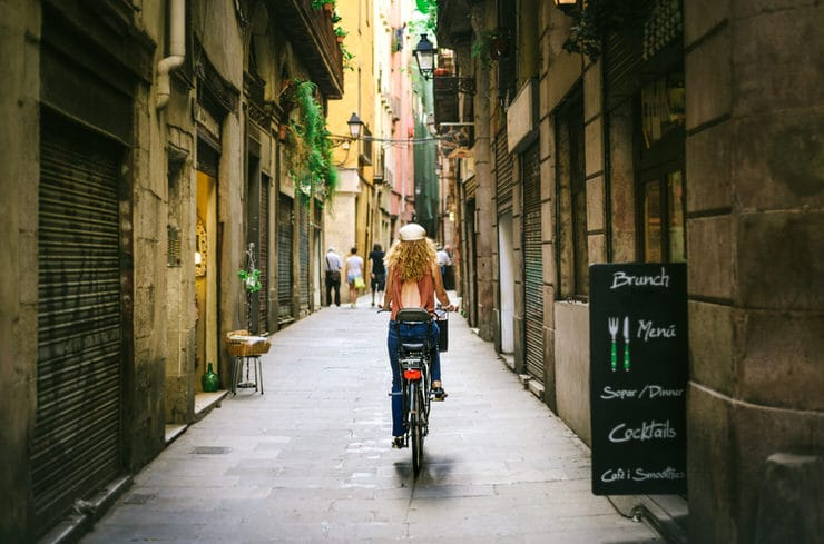 Riding bicycle through old street of Barcelona