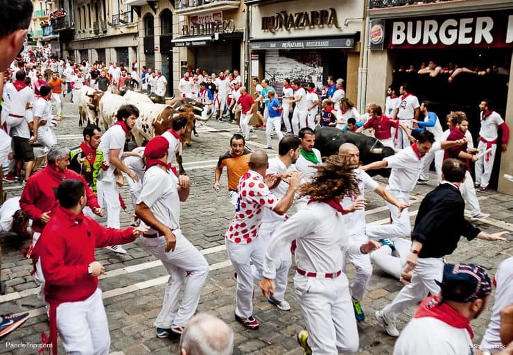 Bulls and people are running in street during San Fermin festival