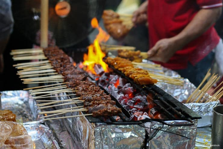 Skewers of chicken cook over hot coals in Singapore's Satay Street food market