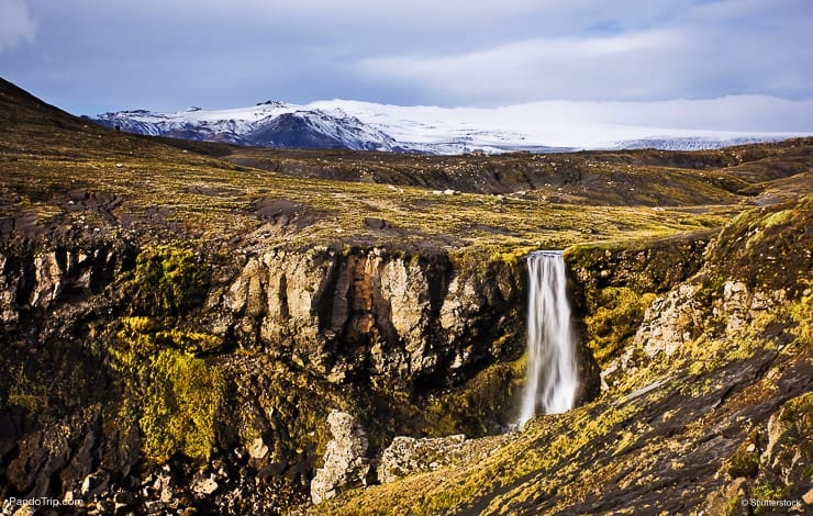 Waterfall and Eyjafjallajokull volcano in background. Iceland
