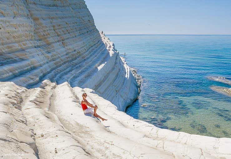 Woman sitting on a slope of white cliff called Scala dei Turchi in Sicily, Italy
