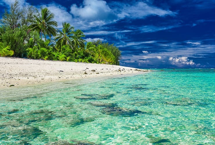 Beach with white sand and black rocks on Rarotonga, Cook Islands