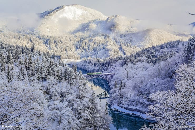 A local train of JR Tadami railway line goes through the snowy mountainside