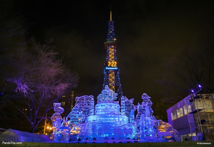 Illuminated snow sculptures during Sapporo Snow Festival with Sapporo TV tower in the background. Sapporo, Hokkaido, Japan