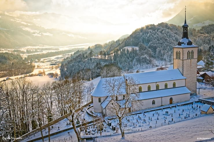 Picturesque snow-covered mountain landscape near the castle of the Gruyeres with an old church in the foreground. Winter in Switzerland