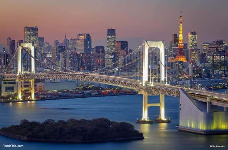 Rainbow Bridge and Tokyo tower in the background at night. Odaiba, Japan